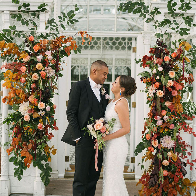 Bride and Groom with Wedding Flower Arch