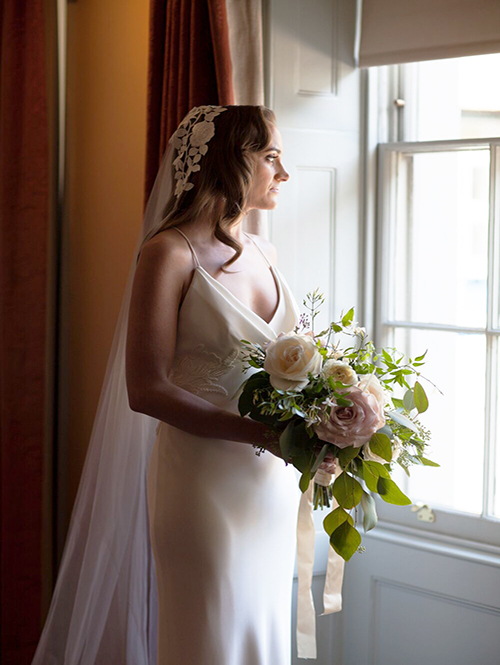 Bride Holding Bouquet at Window